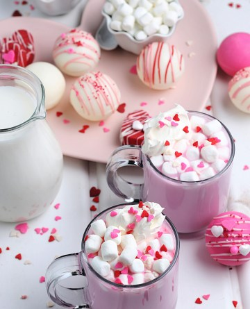 2 cups of pink hot chocolate and Valentine's Day Hot Chocolate bombs on a table