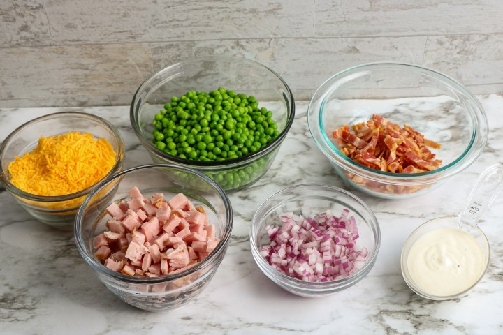 ingredients for classic ham and pea salad in glass bowls