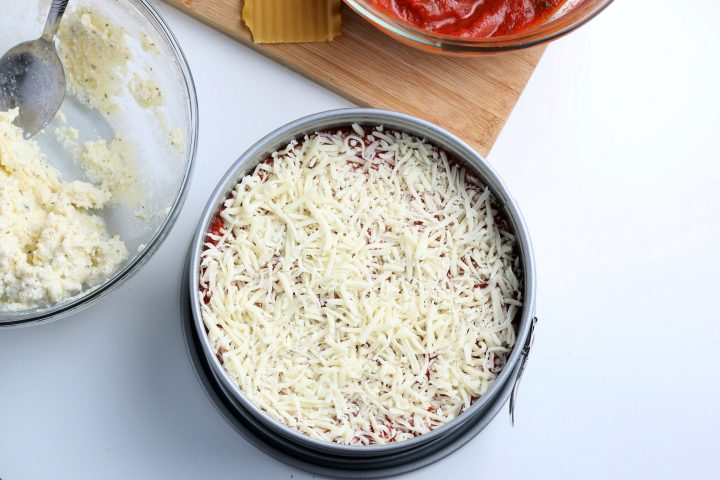 shredded cheese added on top of red sauce