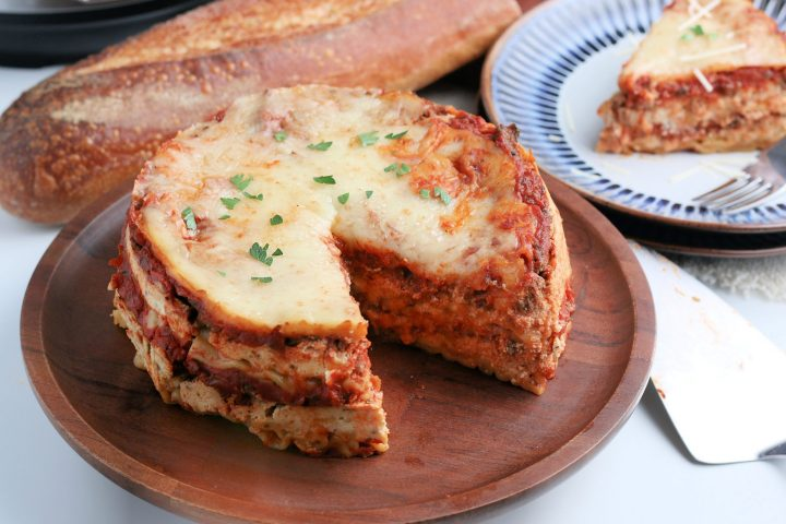 intant pot lasagna on a cutting board with a piece removed