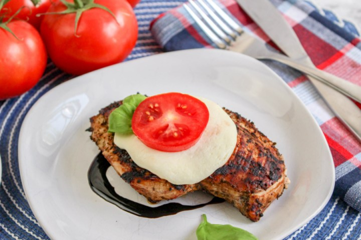 Grilled Caprese Chicken on plate with slice of cheese and tomato