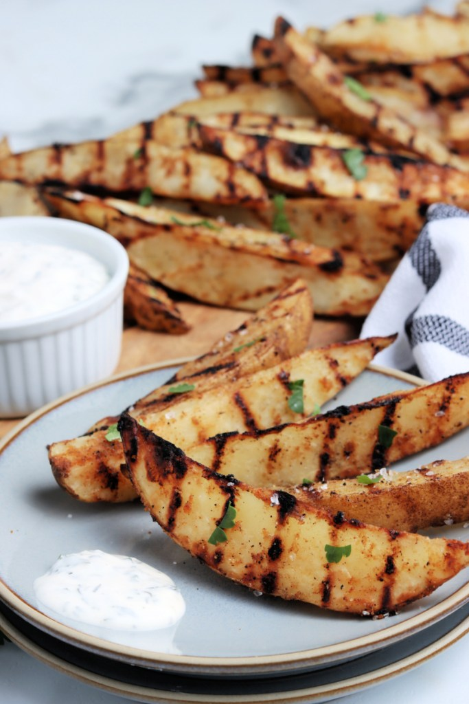 Grilled potato wedges on a plate with dip