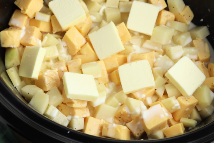 cubed potatoes, cheese and butter in slow cooker