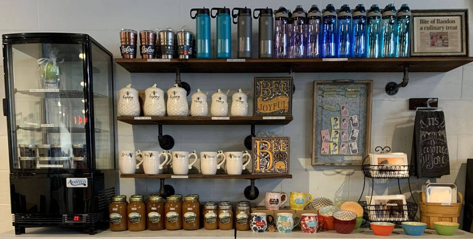 Bottles and cups on shelves with honey stored below
