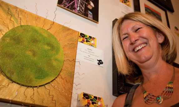 "Mixed media artist Leslie Louise Grandclaudon proudly displays her piece ""Sun Burst"" during the Canoga Park ARTrageous Art Walk in Canoga Park, Calif. on July 20, 2012. The community event was designed to bring the public and the artists together."