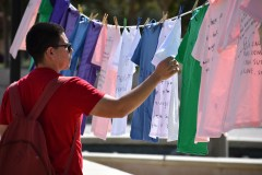 Kevin Romero takes a moment to stop and consume the many messages of domestic abuse that others have left behind at the clothesline project. Photographed at Rocky Young Park at Pierce College in Woodland Hills, Calif. by Pablo Orihuela on Oct., 10, 2019.