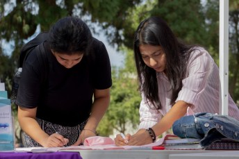(Left to right) Gagandeep Kaur and Bushra Hannan write messages on shirts during the Clothesline Project on Oct. 16, 2019 in Rocky Young Park at Pierce College in Woodland Hills, Calif. Hosted by ASO, the Diversity Committee and B.R.A.V.E., this event brings awareness to survivors of abuse by displaying messages or stories written by students. Photo by Angelica Lopez.