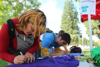 Vicky Aranda and Rodrigo Arratia focus as they design their shirts at The Clothesline Project event at Pierce College Woodland Hills, Calif. on Oct. 16, 2019. Photo by: Kamryn Bouyett