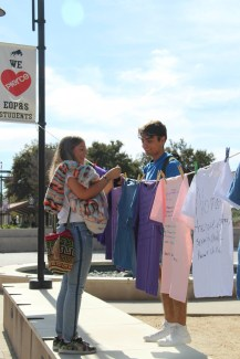 Violeta Bermudez and Rodrigo Arratia help each other hang up their finished t-shirts on the Mall Walkway at Pierce College Woodland Hills Calif. on Oct. 16, 2019. Photo By: Kamryn Bouyett