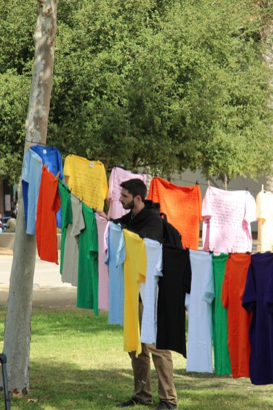 Joe Kananack peers at a yellow tee at the Clothesline Project at Pierce College Woodland Hills Calif. on Oct. 16, 2019. Kananack was going to pass the event but seemed to stop and read the stories that were written on the t-shirts. Photo by: Kamryn Bouyett