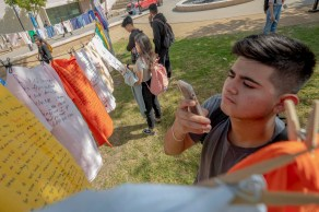 Josue Morales takes a picture of the displayed t-shirts at Rocky Young Park during the Clothesline Project on Wednesday, October 16, 2019, in Woodland Hills, Calif. (Photo by Kevin Lendio)