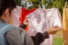 Students of Pierce College reads the hand-written words printed on a shirt at Rocky Young Park during the Clothesline Project on Wednesday, October 16, 2019, in Woodland Hills, Calif. (Photo by Kevin Lendio)