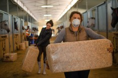 (Right to left) Victoria Lacagnina and Erin Leon carry a bag of shavings inside the stable located at Pierce College, on Friday, Oct. 11, 2019, in Woodland Hills, Calif. Photo by Kevin