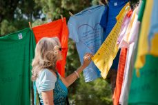 Barbara Anderson, President of the Academic Senate, looks at the shirts hung up for the Clothesline Project hosted by ASO in Rocky Young Park at Pierce College in Woodland Hills, Calif., on Oct. 16, 2019. Photo by Katya Castillo.