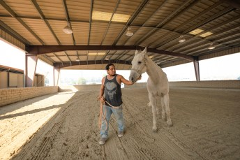 Eli Jordan walks his horse at the Pierce College Equestrian Center in Woodland Hills, Calif. on Oct. 11, 2019. Jordan evacuated from Porter Ranch along with her wife and their 4 horses due to the Saddleridge Fire. Photo by Kevin Lendio.
