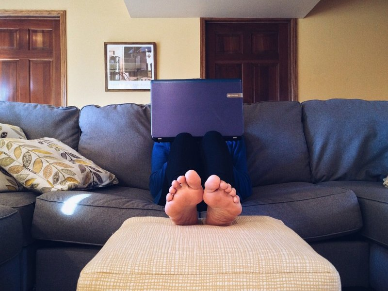 Couchsurfing guest with a laptop on a couch