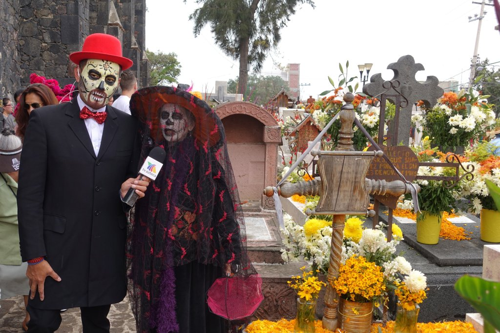 a news reporter interviewing a local. Both are dressed in costume with faces painted to look like skulls