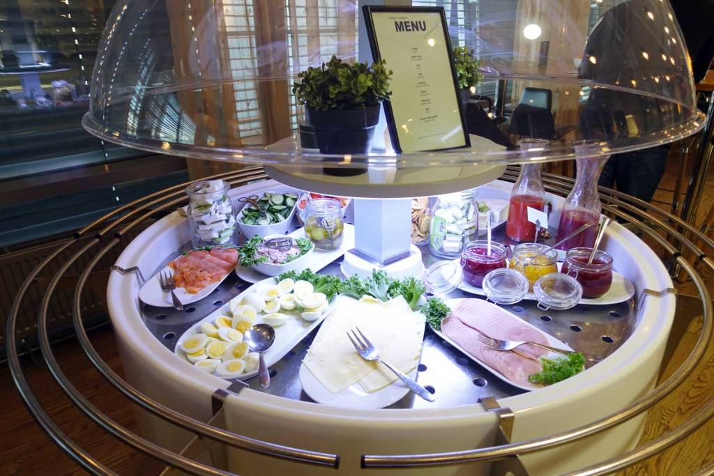 OSL Lounge food trays with eggs, salmon, meats, and salad dressings