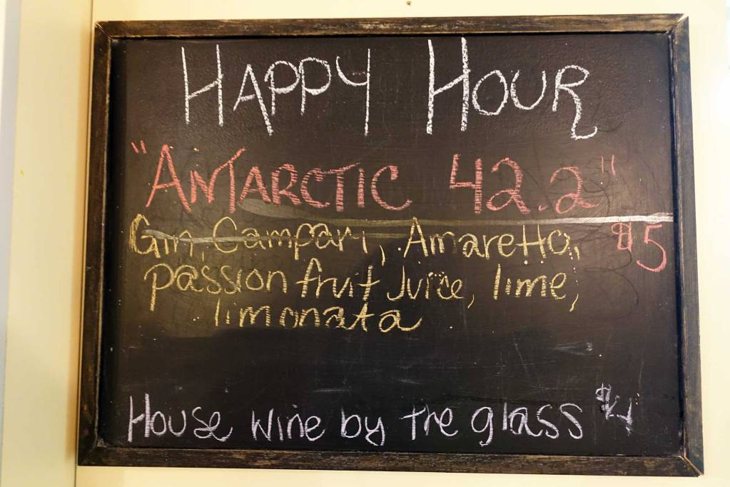 A happy hour sign in the bar on the ship that shows the commemorative antarctica marathon drink specials.