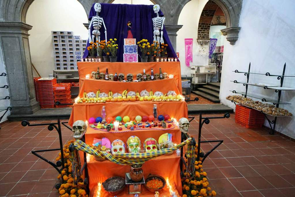 A day of the dead ofrenda at la pasteleria ideal decorated with bread, photos, and skulls