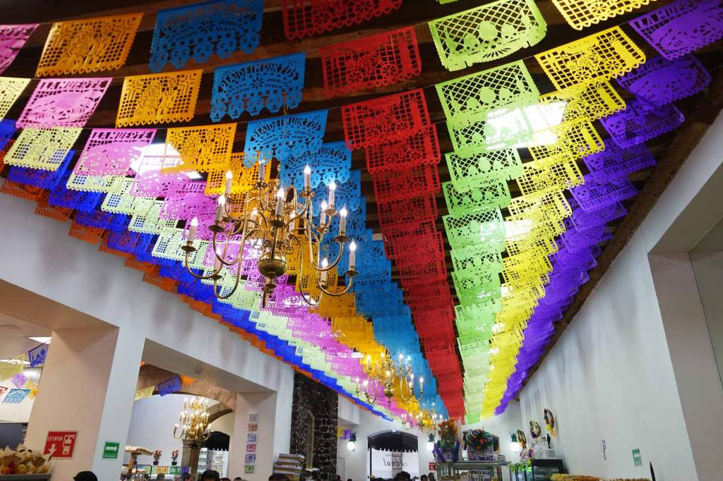 papal picado - colorful paper decorations on the ceiling