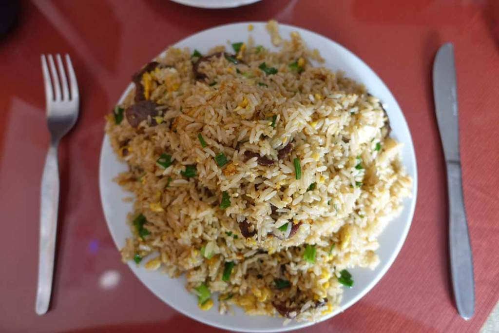 A plate of chaufa at a chifa restaurant. A very large plate of rice. Chifa has become authentic peruvian food