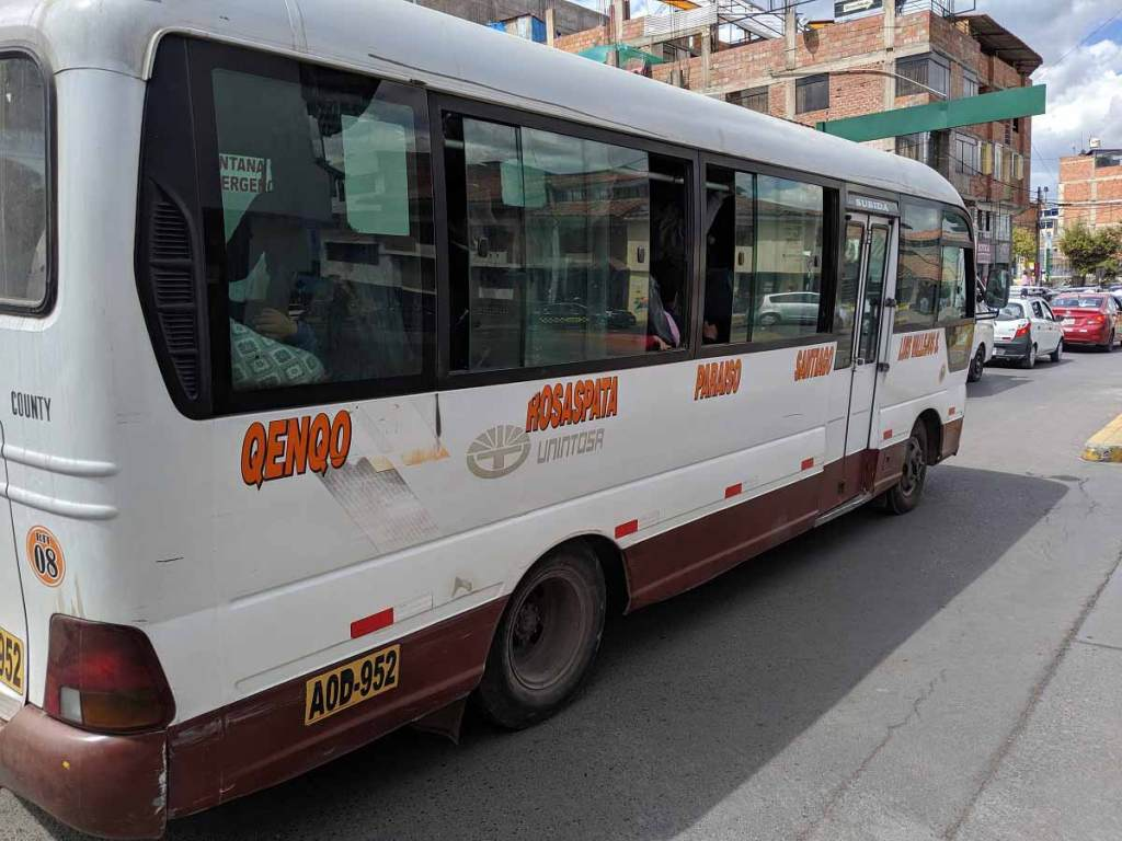 A cusco bus with the major stops printed on the side, including Qenqo, Rosaspata, Paraiso, and so on.