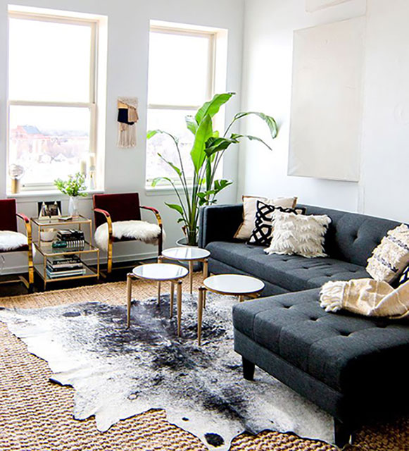 Cowhide rug layered on natural base rug from https://www.graciousstyle.com/blogs/rug-basics-selecting-size/