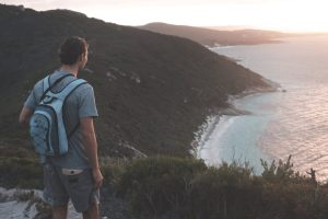 unrecognizable male hiker enjoying seascape from grassy hilltop at sundown