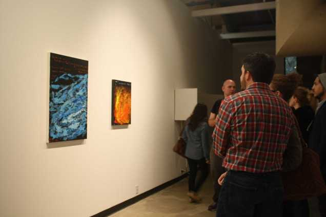 """Guest admiring Donald Myers """"Game of Life"""" (Left) and """"Hello World"""" (Right) at the opening of Nexus senior art exhibition on Thursday, May 14 at Todd Madigan Gallery"""