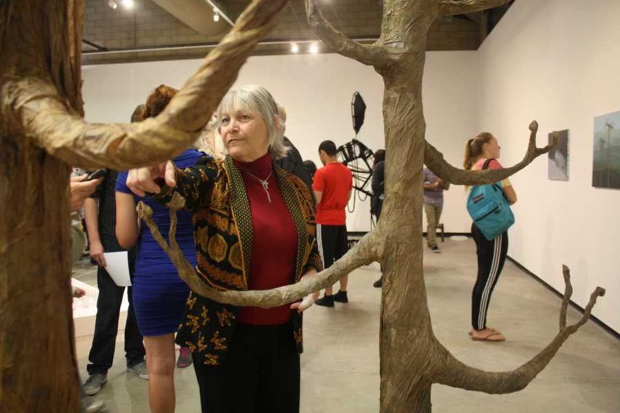 Katherine Cutts explaining the work behind The Tale of Two Trees  during the opening of Nexus senior art exhibition on Thursday, May 14 at Todd Madigan Gallery