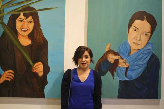 """Perla V. Diaz taking a photo with her paintings """"Weathering life's strom"""" during the opening of Nexus senior art exhibition on Thursday, May 14 at Todd Madigan Gallery"""