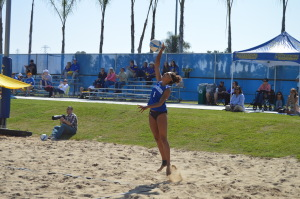 Senior Danika Youngblood serves a ball in a match at the Student Recreation Center Barnes Beach Volleyball Complex on March 7. Photo by Janeane Williams/The Runner