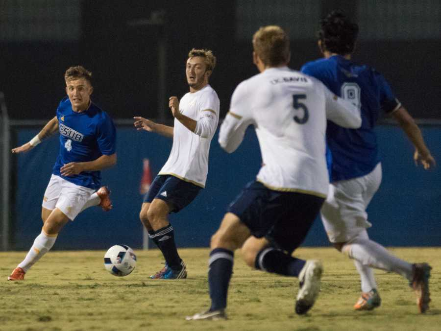 CSUB's senior defender Jamie Carey-Morrell dribbles against UC Davis' Matt Baringer as Chase Rhode and CSUB's Hugo Vinales look on during the first half of Thursday's game at CSU Bakersfield.