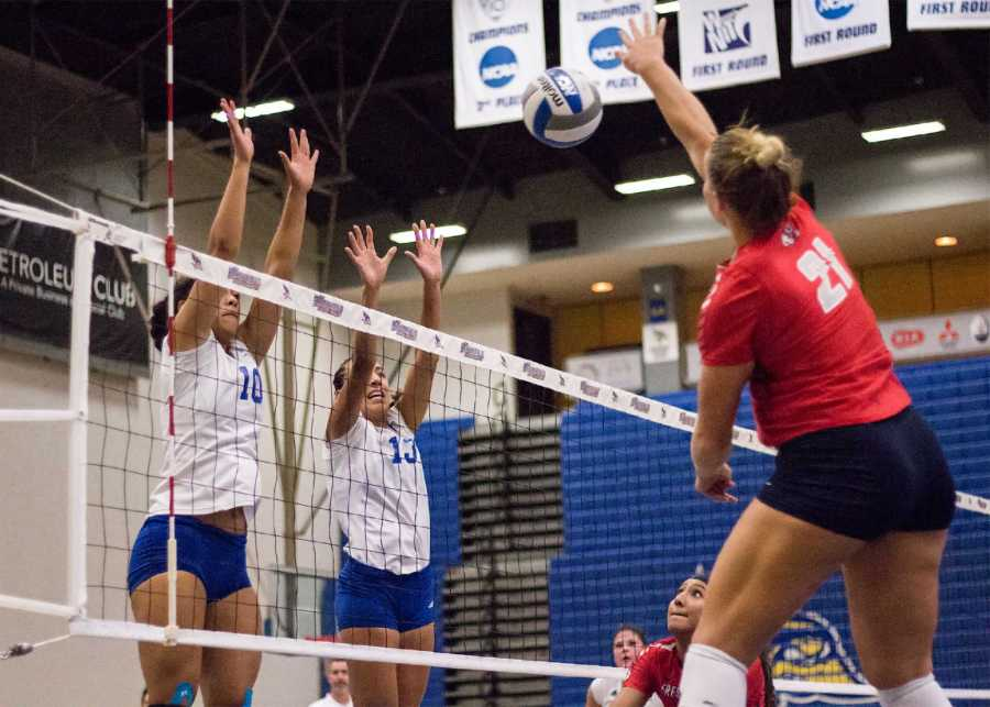Junior outside hitter Briannah Mariner and redshirt-senior middle blocker Sydney Haynes go up to block a kill attempt against Fresno State on Sept. 12 in the Icardo Center. Photo by Scot Swan/The Runner