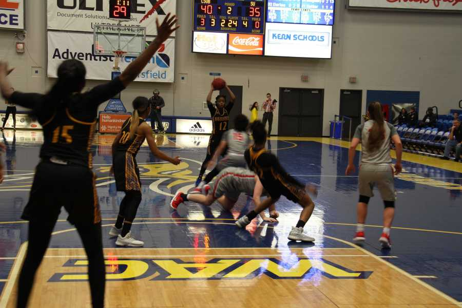 No. 12 Alexxus Gilbert looks for an open pass as players recover from falls on the court during the Jan. 27 game versus Seattle University.