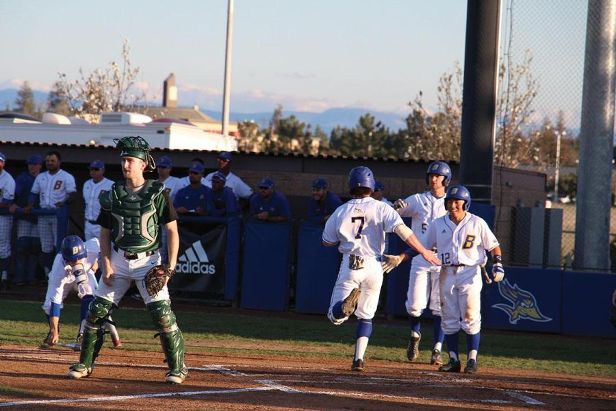 No. 5 Alec Daily and No. 12 Austyn Tengan greet No. 7 Andrew Penner, in the 1st inning after he crosses home plate.