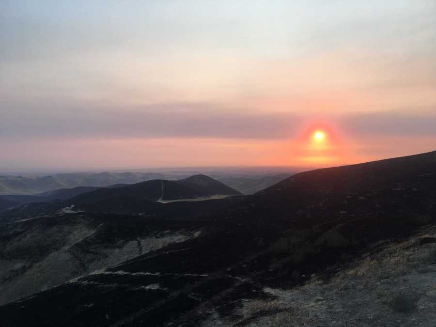Smoke+filled+sky+turns+the+sun+orange+with+burned+foothills+under.+%0A