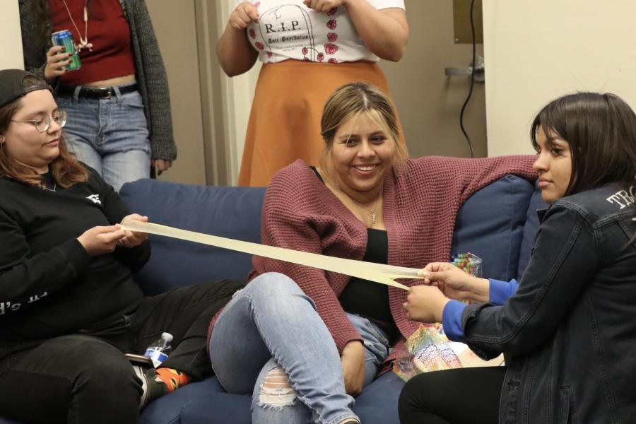 From left: Karina Miranda, Daisy P., and Yuridiana Pantoja demonstrated a dental dam during the Let's Talk About Sex event on April 10 inside CSU Bakersfield's Multi-Cultural Alliance and Gender Equity Resource Center.
