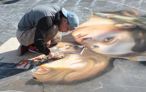 Artist, Shuji Nishimura, works on his piece based on Raphael's Madonna della seggiola on Oct. 19, 2019 during day one of Via Arté at the Market Place.