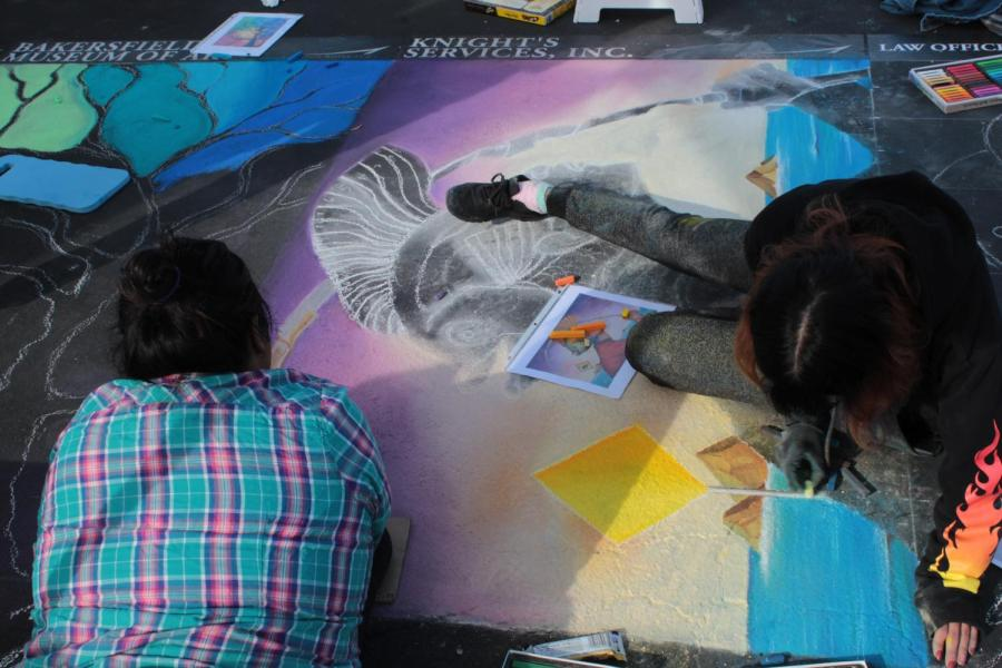 Artist Ana Reyes and and Kaylee Carlson work on their piece on Day 1 of Via Arté at the Market Place.