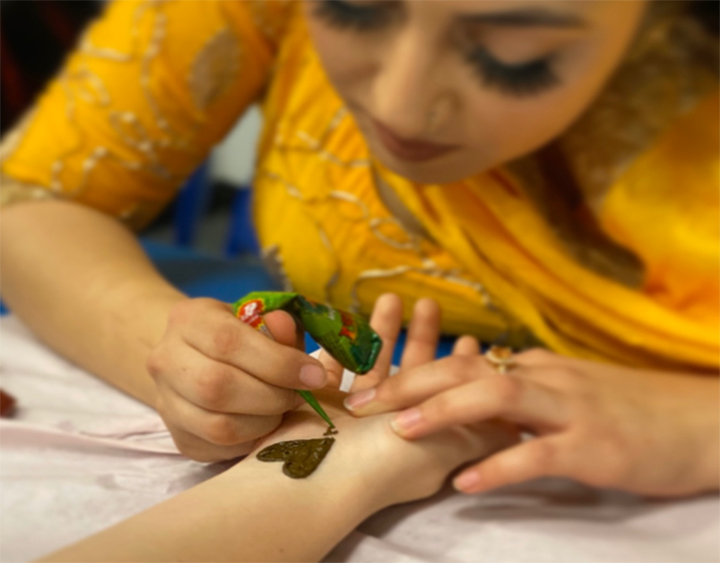 Henna Singh is pictured applying henna tattoo on a student at the Diwali Festival. Henna is a paste made from leaves of Lawsonia inermi.
