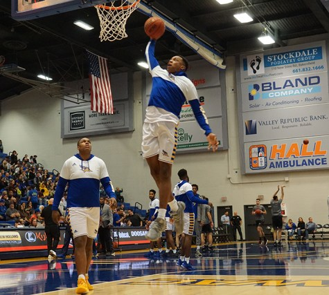 Senior forward Justin Edler Davis goes for a slam dunk during warm ups on Saturday Jan. 25that the Icardo Center