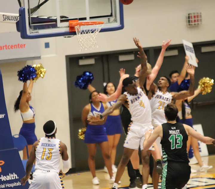 Junior Taze Moore and Junior Greg Lee try to block opponent from making the basket