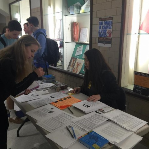 Senior Juliana Yue welcomes students to look at the materials at her table, which highlight women's issues around the globe and stand in solidarity with the female community.