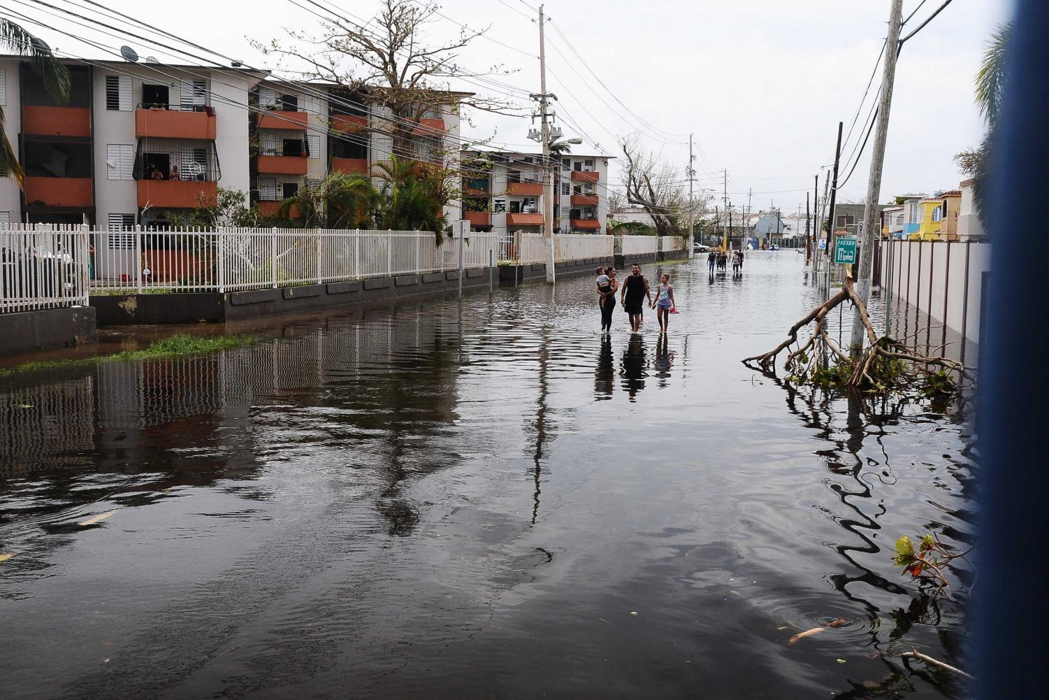 A family walks down the flooded streets of San Juan, Puerto Rico after Hurricane Maria. THE DEPARTMENT OF DEFENSE