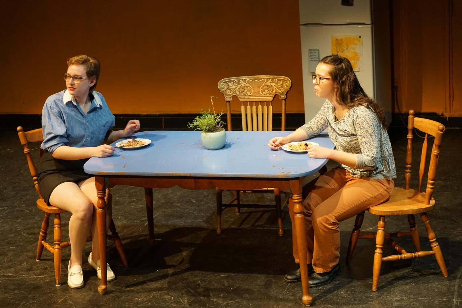 Emmaline (junior Rebecca Perez) and  her daughter Charlotte (junior Devasha Solomon) eat dinner together while discussing Charlotte's upcoming birthday in Kids on the Sidewalk.