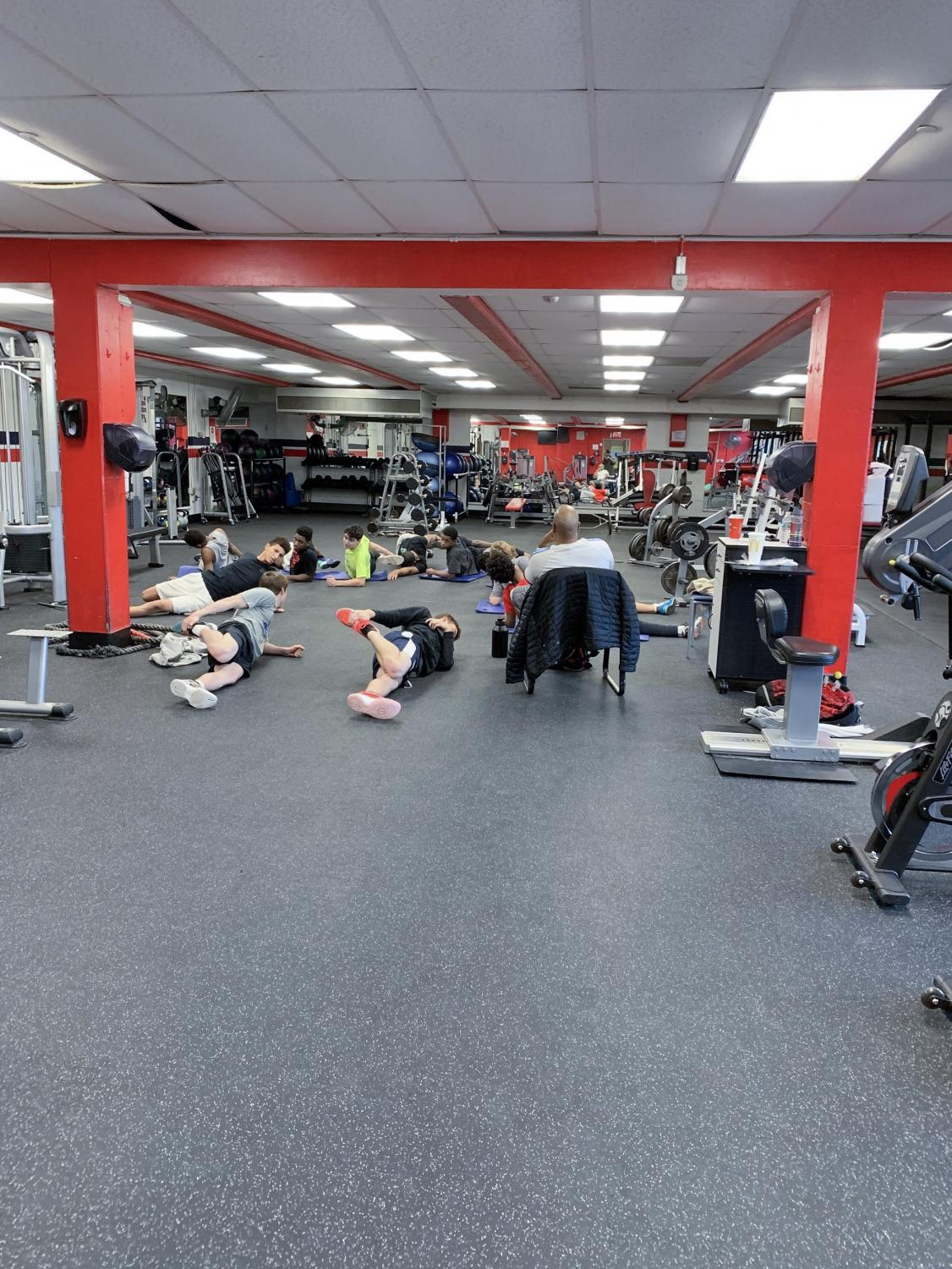 The boys varsity basketball team stretches at an after school practice in the weight room. A variety of workout methods allow athletes to perform at their best.