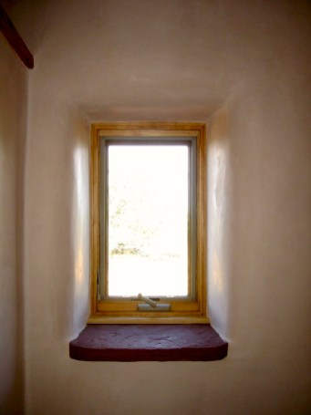 Plaster detail around window set into a Straw Bale wall with a deep stone sill.