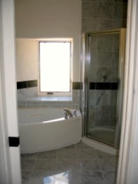 Master Bath tub and shower with half flared window detail.